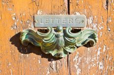 92173648 - old postal brass mailbox gainst a colored wooden door